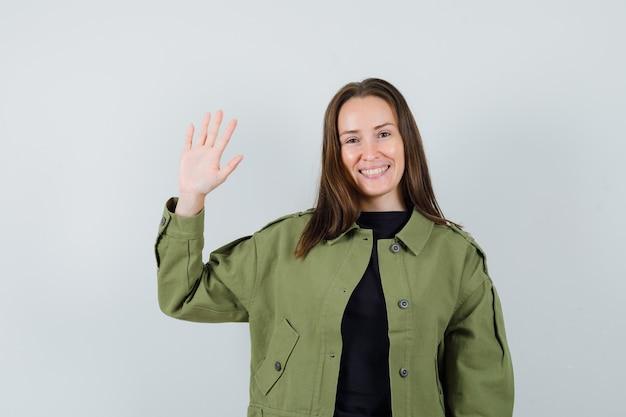 Jonge vrouw in groene jas zwaaiende hand voor groet en op zoek vrolijk, vooraanzicht.