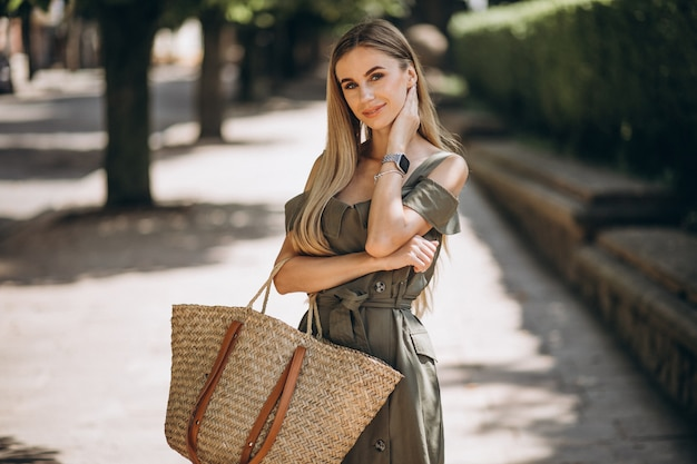 Jonge vrouw in groene jurk buiten in park