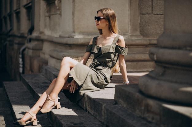 Jonge vrouw in groene jurk zittend op de trappen van een oud gebouw