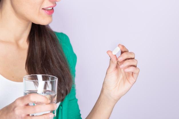 Jonge vrouw in groene trui en wit overhemd met een pil en een glas water. geneeskunde en gezondheidszorg concept.