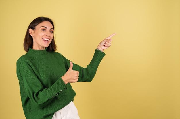 Jonge vrouw in groene warme trui die met de vingers naar rechts wijst