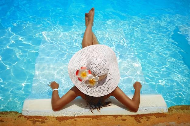 Jonge vrouw in grote witte hoed rustte op een ligstoel in het zwembad
