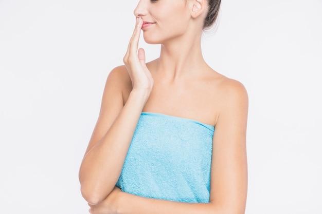 Jonge vrouw in handdoek met hand op de lippen