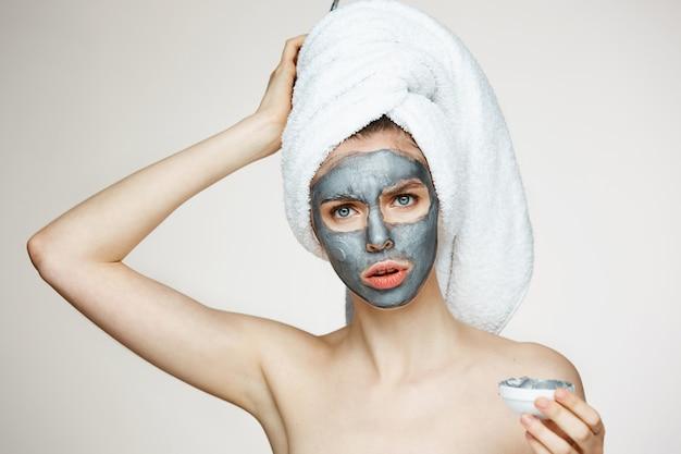 Jonge vrouw in handdoek op hoofd met gezichtsmasker het fronsen. schoonheid en huidverzorging.