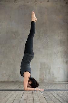 Jonge vrouw in handstandoefening