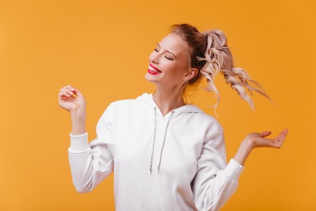 Jonge vrouw in heerlijke bui lacht met haar ogen dicht