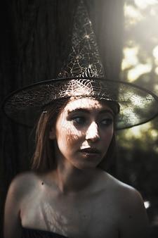 Jonge vrouw in heksenhoed in park