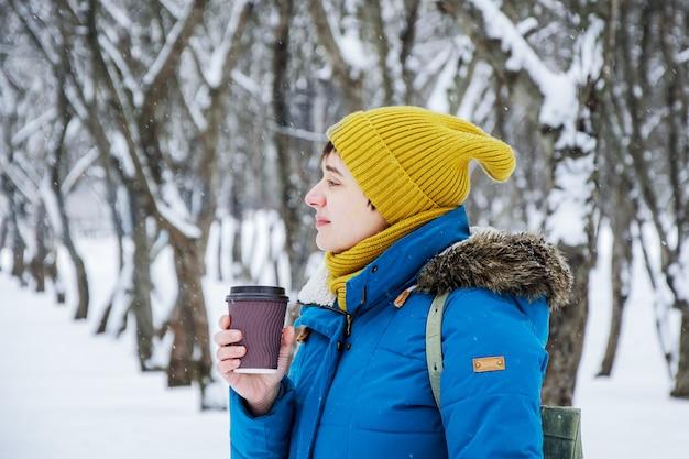 Jonge vrouw in heldere winter glb en jas in profiel op een wandeling in winter park met papieren kopje koffie om mee te nemen.