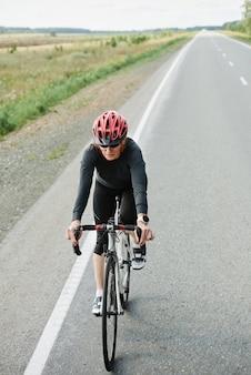 Jonge vrouw in helm rijden op een fiets op een weg tijdens sportcompetitie