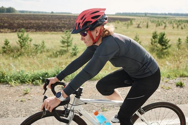 Jonge vrouw in helm rijdend op een sportfiets op een weg die ze deelneemt aan competitie