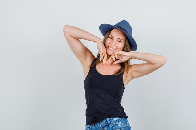 Jonge vrouw in hemd, korte broek, hoed hand in hand in de buurt van wangen en ziet er vrolijk uit