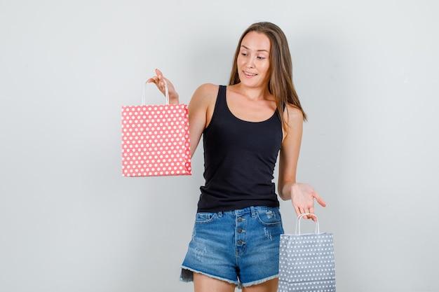 Jonge vrouw in hemd, korte broek met papieren zakken en op zoek blij