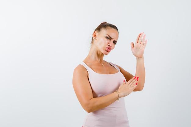 Jonge vrouw in hemd met karate hakken gebaar en op zoek naar zelfverzekerd, vooraanzicht.