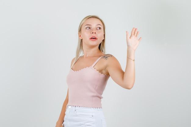 Jonge vrouw in hemd, minirok zwaait met de hand om gedag te zeggen en ziet er zelfverzekerd uit