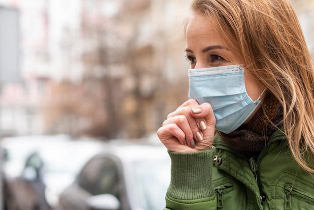 Jonge vrouw in het beschermende steriele medische masker hoesten