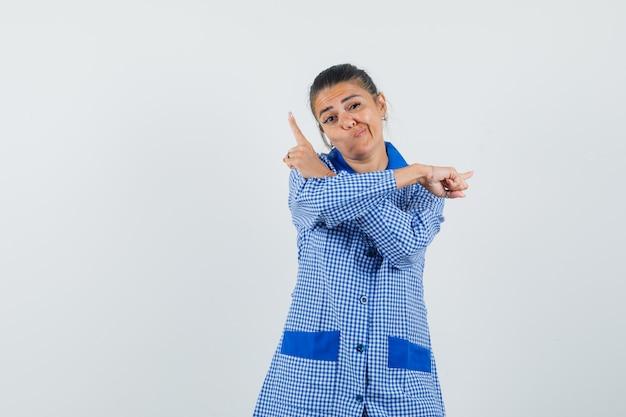 Jonge vrouw in het blauwe overhemd van de gingangpyjama dat verschillende richtingen met wijsvingers toont en mooi, vooraanzicht kijkt.