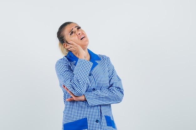 Jonge vrouw in het blauwe overhemd van de gingangpyjama, hand leunend op de wang, die zich in het denken bevindt stelt en uitgeput kijkt, vooraanzicht.