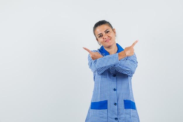 Jonge vrouw in het blauwe overhemd van de ginghampyjama die tegengestelde richtingen met wijsvingers richt en er mooi uitziet, vooraanzicht.
