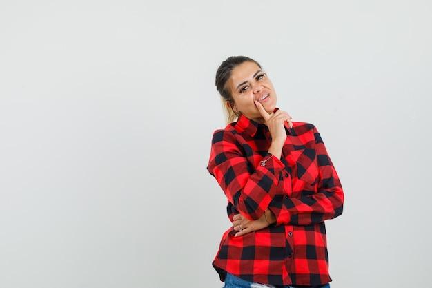 Jonge vrouw in het denken pose in geruit overhemd, korte broek en op zoek verstandig. vooraanzicht.