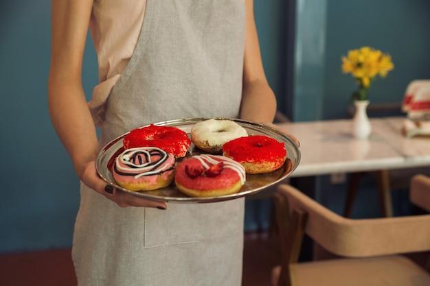 Jonge vrouw in het dienblad van de schortholding met donuts