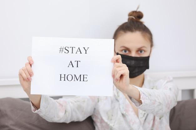 Jonge vrouw in het document van de beschermingsmaskerholding met verblijf thuis in haar huis. stop virusquarantaine thuis.