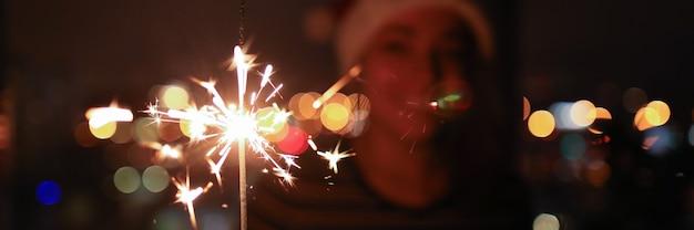 Jonge vrouw in het donker houdt verlichte sterretjes in haar handen