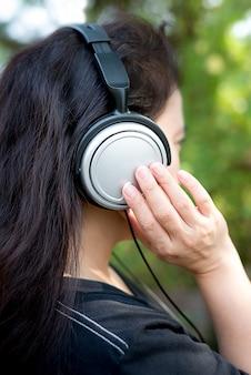 Jonge vrouw in het genieten van muziek door hoofdtelefoon