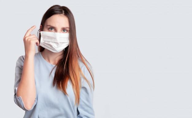 Jonge vrouw in het masker van de gezichts medische chirurgie. coronavirus protection, covid-19, virus, griep, kon concept. draagt, verwijdert een medisch masker.