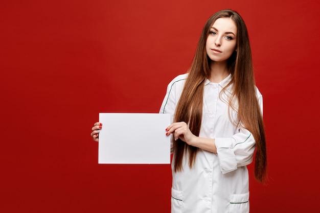 Jonge vrouw in het medische eenvormige stellen met een leeg wit blad van document bij de rode geïsoleerde achtergrond, exemplaarruimte voor uw tekst. gezondheidszorg concept