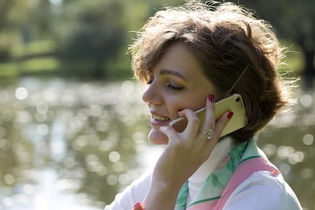 Jonge vrouw in het park spreekt via de mobiele telefoon. leuk meisjesportret in franse stijl.