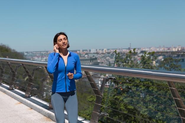 Jonge vrouw in het passen van sportkleding op de brug op warme zonnige ochtend hardlopen joggen met koptelefoon gelukkige glimlach, geweldig uitzicht op de stad