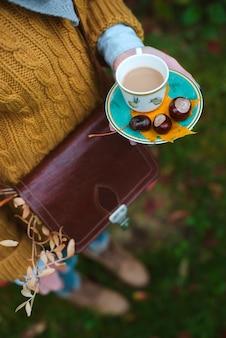 Jonge vrouw in het romantische beeld van de herfst modieuze kleren. het meisje met de pet houdt een kopje koffie met kastanjes op een schoteltje tegen het herfstbladeren.