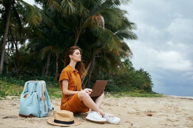 Jonge vrouw in het tropische strand dat laptop met behulp van
