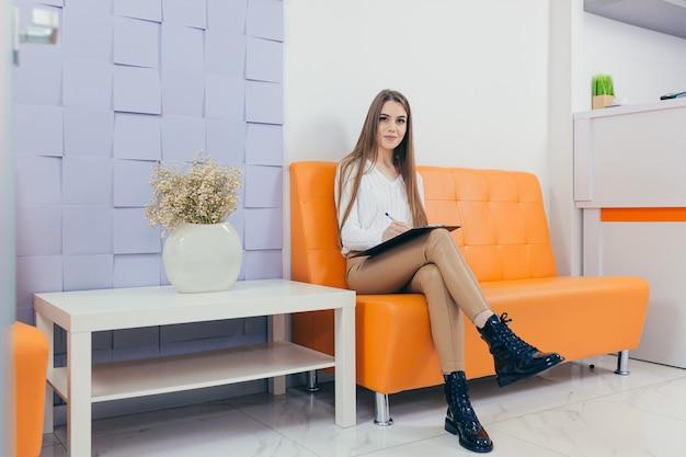 Jonge vrouw in het wachtkamer-interview zittend op de bank in gang van het kantoor van de tandarts