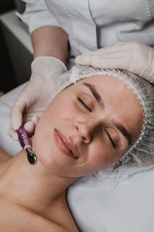 Jonge vrouw in het wellnesscentrum met een huidbehandeling