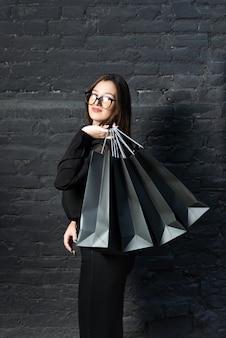 Jonge vrouw in het zwart houdt papieren zakken op zwarte achtergrond. verticaal kader. zwarte vrijdag-concept.
