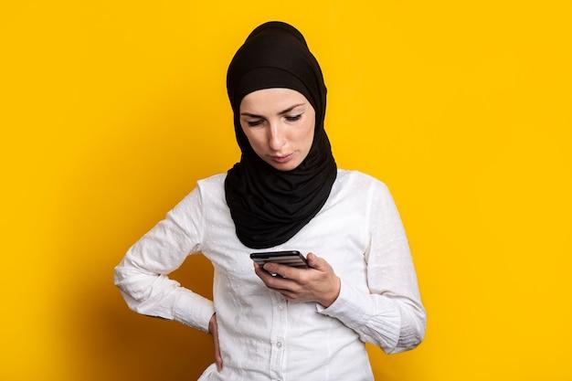 Jonge vrouw in hijab kijkt naar de telefoon op een geel.