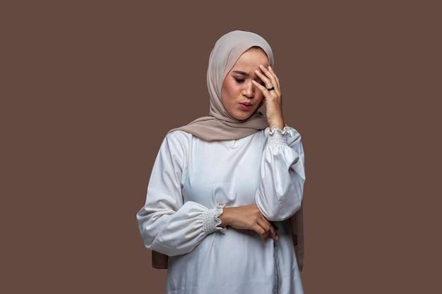 Jonge vrouw in hijab poseren met hoofdpijn, duizelig en droevige uitdrukking.