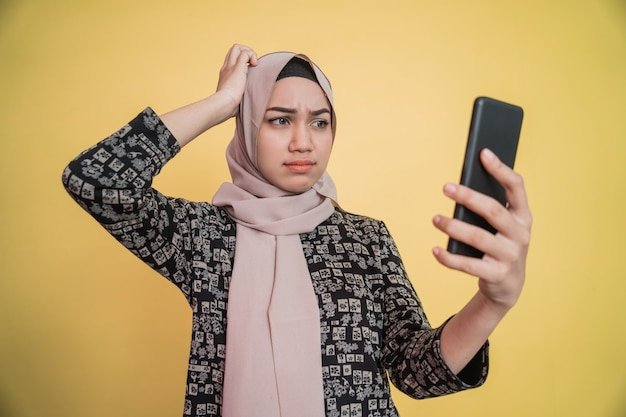 Jonge vrouw in hijab verward terwijl ze naar het scherm van de smartphone kijkt met de hand die haar hoofd krabt