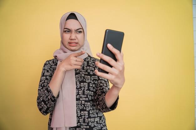 Jonge vrouw in hijab walgt terwijl ze naar het smartphonescherm kijkt met een wijzend handgebaar
