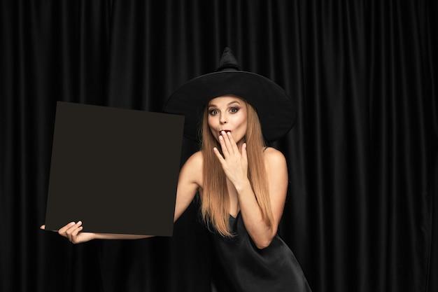 Jonge vrouw in hoed als een heks die zwarte raad houdt tegen zwarte gordijnen