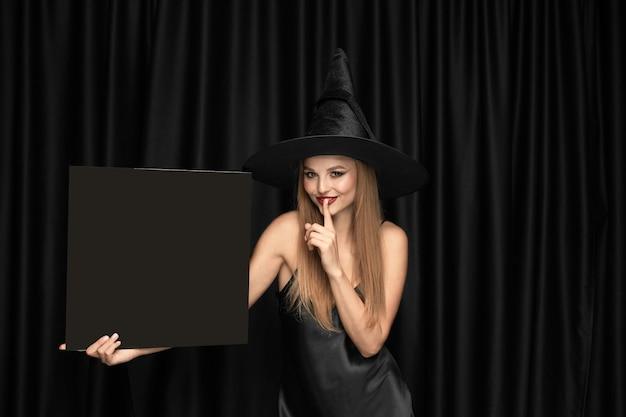 Jonge vrouw in hoed als heks op zwart gordijn