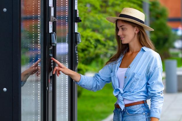 Jonge vrouw in hoed die automaat op de straat met behulp van