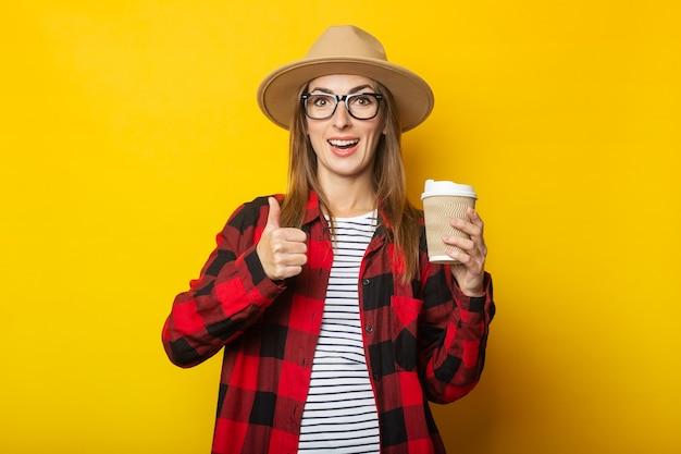 Jonge vrouw in hoed en geruite overhemd document kop met koffie te houden en handgebaar op geel te maken