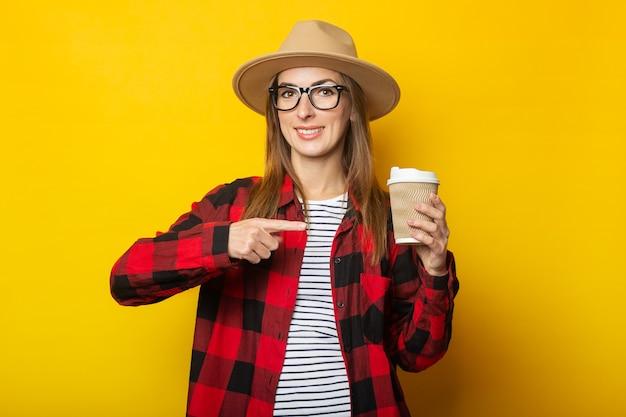 Jonge vrouw in hoed en geruite overhemd document kop met koffie te houden en handgebaar op gele oppervlakte te maken