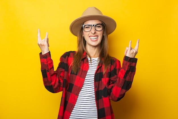 Jonge vrouw in hoed en geruite overhemd rock-'n-roll gebaar maken op geel.