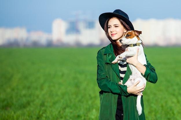 Jonge vrouw in hoed en mantel met hond