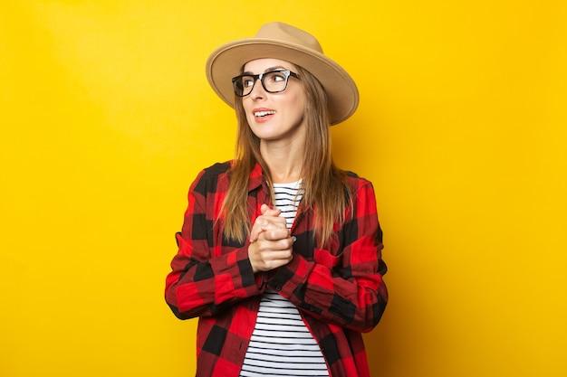 Jonge vrouw in hoed en plaidoverhemd op geel.