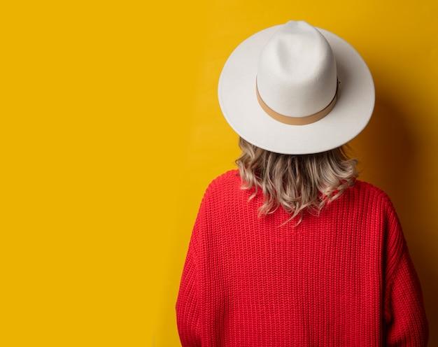 Jonge vrouw in hoed en rode trui