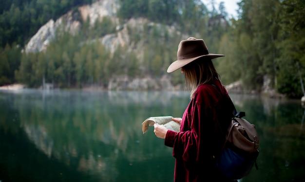 Jonge vrouw in hoed en rood shirt met kaart in de buurt van het meer